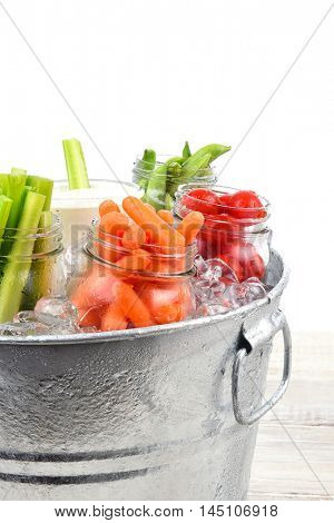 Closeup of fresh vegetables in a metal ice bucket on a rustic wood table, Isolated on white.