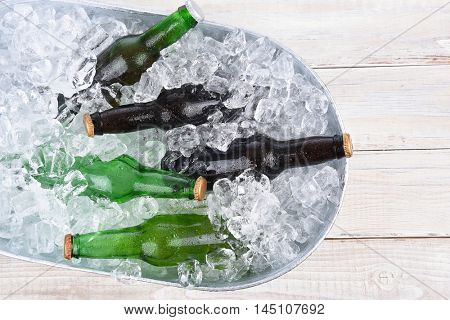 High angle view of a beer bucket filled with ice and assorted beer bottles. Horizontal format with copy space.