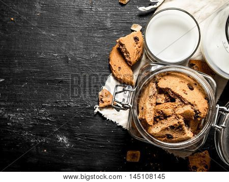 Oatmeal cookies with fresh milk. On a black wooden background.