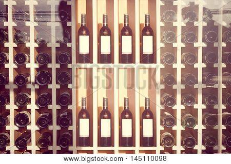 Wine bottles on wooden shelf in wine cellar