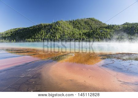Grand Prismatic Spring in Midway Geyser Basin with steam and reflections. Yellowstone National Park Wyoming United States