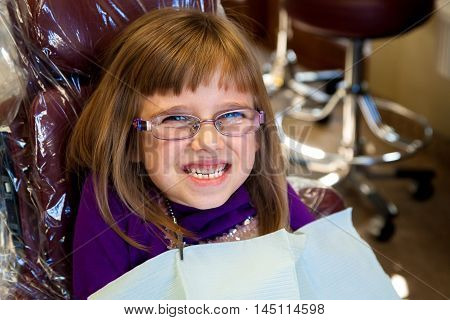 An adorable little girl sits grinning in a dentist chair. She looks happy and excited.