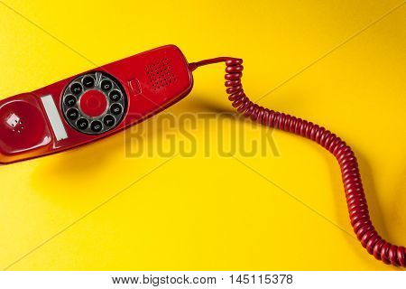 Old red phone off the hook on yellow background