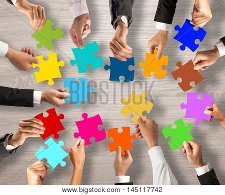 Business people join the colorful puzzle pieces