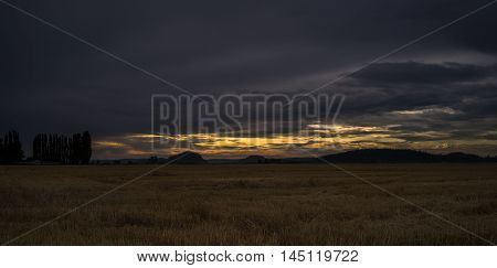Darkness falls on a Skagit Valley field as the sun sets in the distance