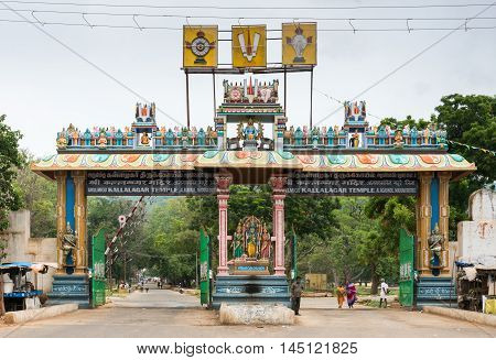 Madurai India - October 19 2013: Monumental entrance gate to domain of Kallalagar Vishnu Temple shows several of his avatars. People in photo.