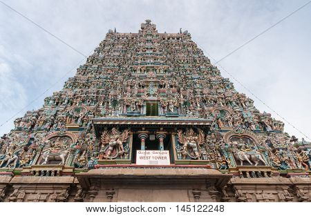 Madurai India - October 19 2013: Vertical shot along the facade of the West Gopuram. End in the sky. Abundance of statues and pallet of pastel colors.