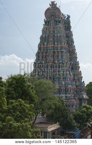 Madurai India - October 19 2013: Closeup of the North Gopuram of the Meenakshi Temple against faint blue sky. Seen from the West. Bottom behind green trees.