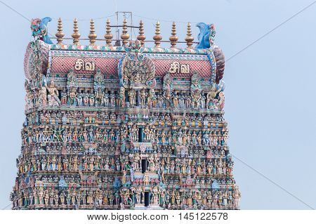 Madurai India - October 19 2013: Closeup of the top of the South Gopuram of the Meenakshi Temple against bluish white skies. Pastel colors and statues.