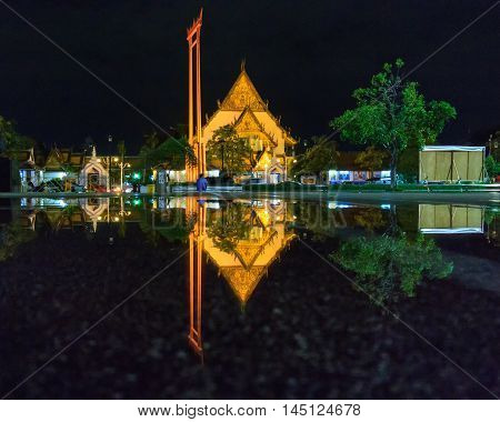 The Giant Swing with Temple of Buddha in Bangkok at twilight time with reflection on the water after hard raining Bangkok Thailand