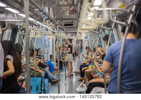 SINGAPORE-JUNE 26: Unidentified people on the Mass Rapid Transit train in Singapore on June 26 2015. The Mass Rapid Transit has 102 stations and is the second-oldest metro system.