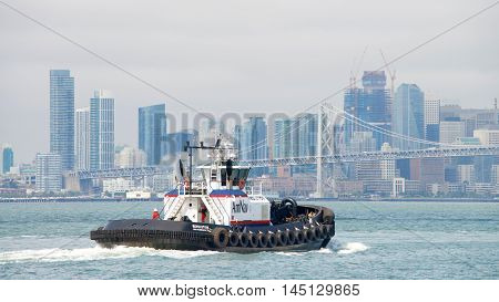 Oakland CA - August 23 2016: Tugboat REVOLUTION in the San Francisco Bay after departing the Port of Oakland. City of San Francisco in the background.