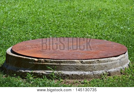Closeup of a manhole with rusty lid and green grass