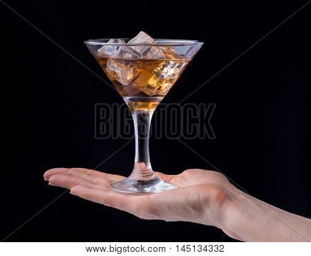 hand holding glass of brandy isolated on black