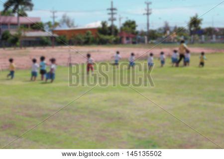 Student Kindergarten. Blur blurred student Kindergarten running on grass in school Teachers have run lead.