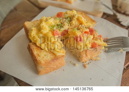 close up scrambled eggs on toasted bread.