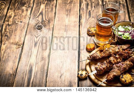 Pork kebab with beer and vegetables. On wooden background.