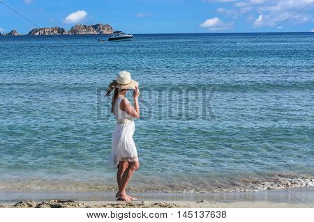 Young woman on the beach overlooking the sea in the background a motorboat.