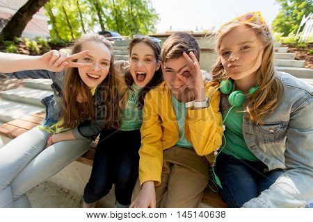friendship and people concept - happy teenage friends or high school students having fun and making faces
