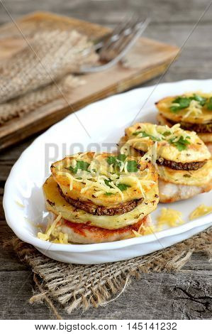 Fried turkey meat with spice potatoes, zucchini and cheese on a plate and on a burlap. Fork and knife on a kitchen board and on wooden table. Fried turkey meat with vegetables and cheese recipe