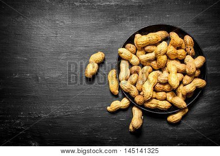 Peanuts in the old plate. On the black wooden table.