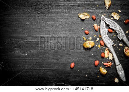 Shelled peanuts with the shell and a Nutcracker. On the black wooden table
