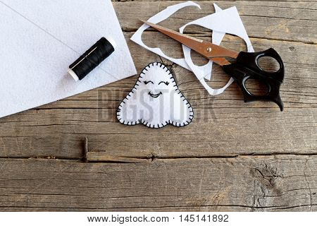 Little white Halloween ghost decor, scissors, black thread, pieces and scraps of felt on old wooden background. Sewing kit. Kids art in autumn holiday. Halloween ghost tutorial. Closeup