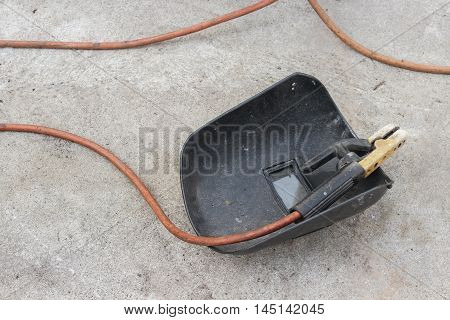 welding mask still life of rod-holder with cable and electrode for electric arc  on a cement floor.