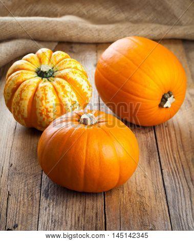 fresh yellow pumpkins on wooden rustic board