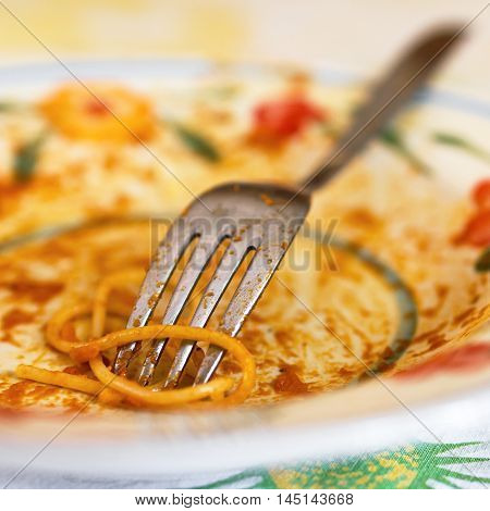 Empty plate with fork after eaten Spaghetti. Defocused blurry background.