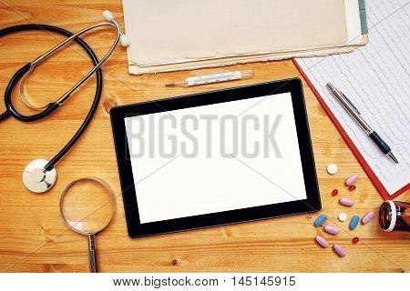 Tablet computer with blank screen on doctor's office desk as copy space top view of general medical practitioner accessories in workspace.