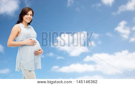 pregnancy, motherhood, people and expectation concept - happy pregnant woman touching her big belly over blue sky and clouds background