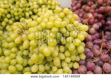 Green-yellow and red grapes for sale at city farmers market