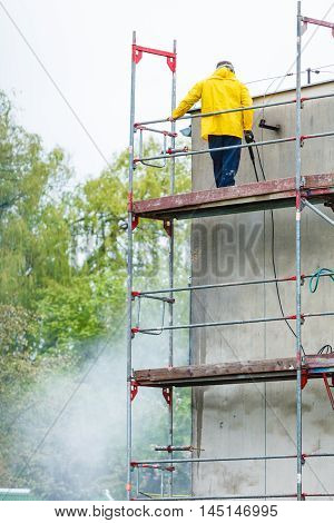 Man cleaning wall. Scaffolding construction site in progress. Building renovation. Cleaning dirtiness.