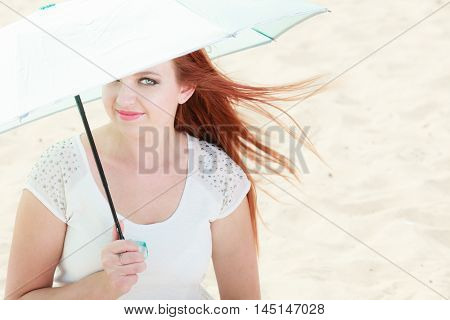 Redhaired Girl Sitting Under Umbrella On Beach.