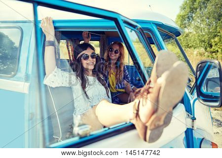summer holidays, road trip, vacation, travel and people concept - smiling young hippie women resting in minivan car