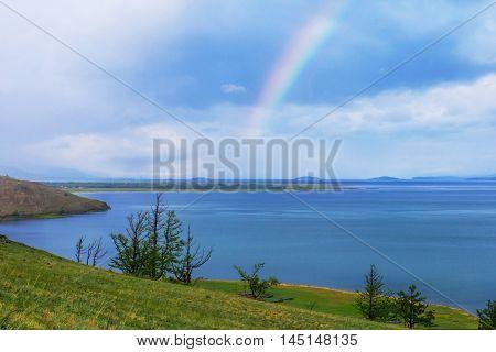 Rainbow over calm water of taiga lake, Baikal, Russia