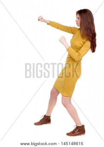 skinny woman funny fights waving his arms and legs. Long-haired brunette in a mustard-colored dress hands fights.