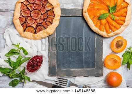 Homemade apricot and figs galette made with fresh organic apricotes and fig jam on wooden table, top view