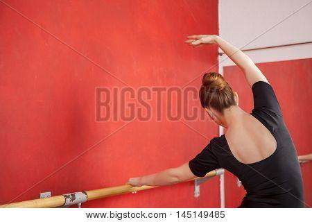 Dancer Stretching At Barre In Ballet Studio