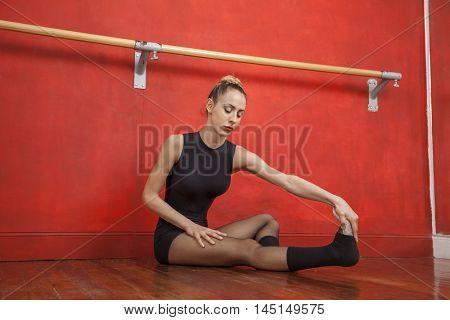 Female Ballet Dancer Stretching In Rehearsal Room