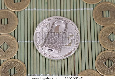 Silver-plated Litecoin and padlock on a wooden tablecloth. Selective focus.