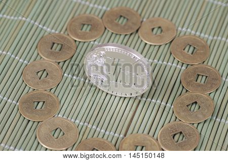 Silver-plated Litecoin on a wooden tablecloth. Selective focus.