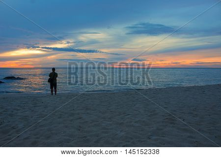Sunrise morning time before cameraman on the beach. beautiful Colorful sky and water in lake reflected. Select focus with shallow depth of field
