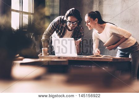Technologies making business easier. Confident young man and woman looking at laptop and smiling while both standing near the desk in creative office