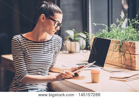 Technologies making life easier. Confident young woman holding digital tablet and looking at it while sitting at the wooden counter in cafe or creative office