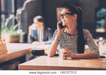 Carefree talk with friend. Cheerful young woman talking on phone and smiling while enjoying coffee in cafe