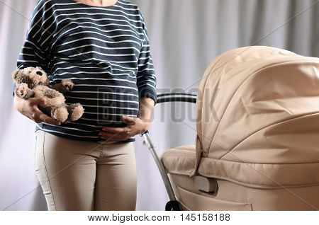 In Anticipation Of Motherhood. Pregnant Woman Standing Near A Pram And Holding A Toy Bear On Gray Ba