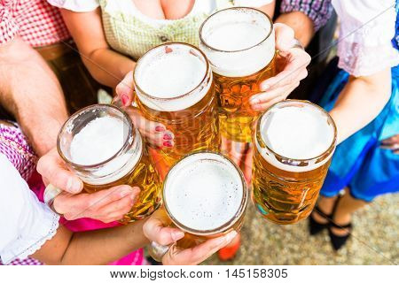Clinking glasses with beer in Bavarian beer garden, close-up on five beer glasses