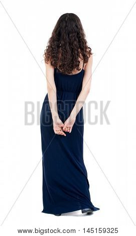back view of standing young beautiful woman. dark curly girl in a blue evening dress is standing with his hands crossed behind his back.